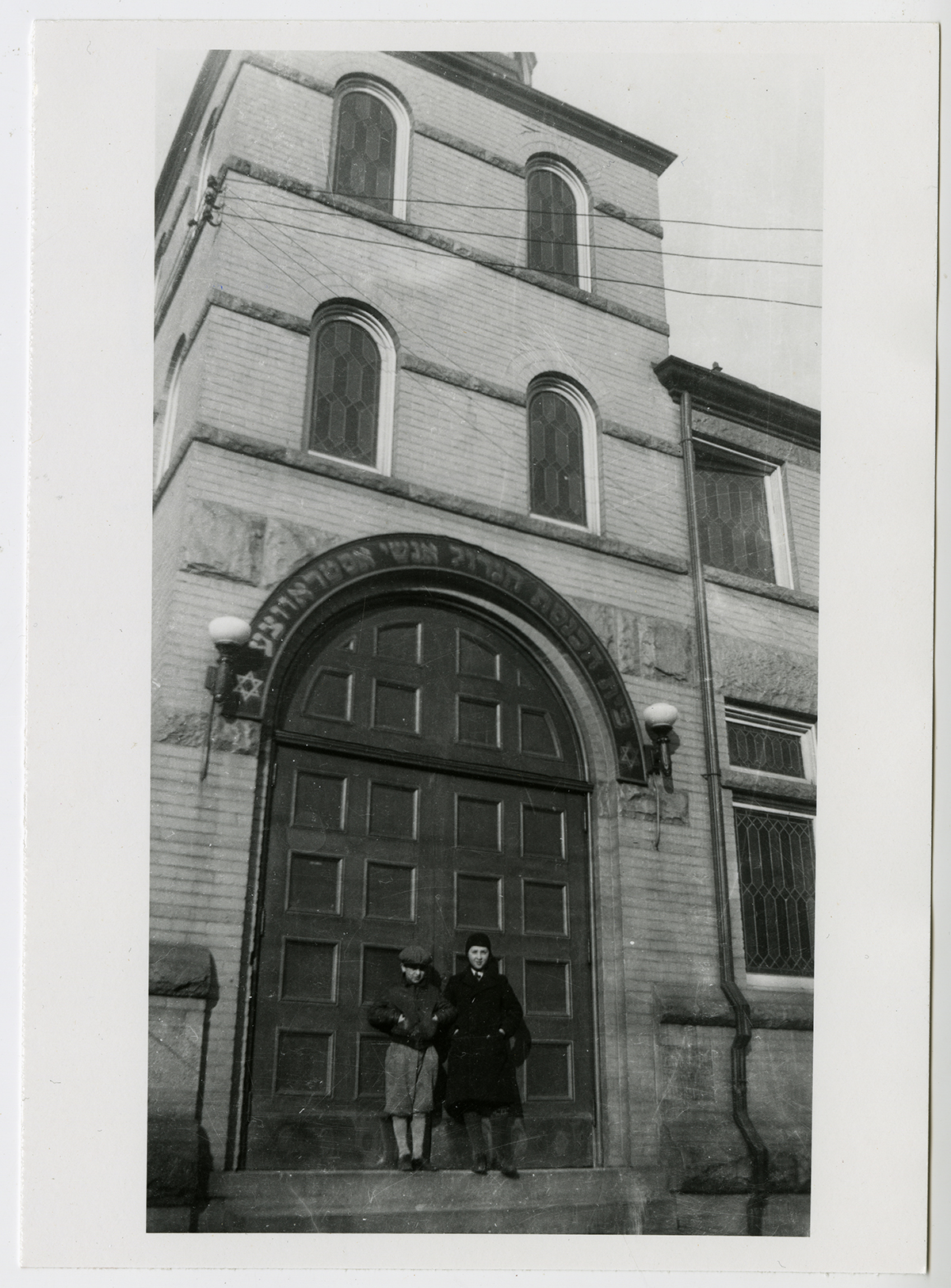 Gordon Perlmutter and Gurion Hyman at the entrance of the Ostrovtzer Synagogue in 1938. Both Perlmutter and Hyman grew up in the area and later worked there too. Perlmutter became a dentist in the community, and Hyman worked in the family business and helped operate Hyman's Art and Book Shoppe, located on Spadina Avenue.   OJA, item 1180.