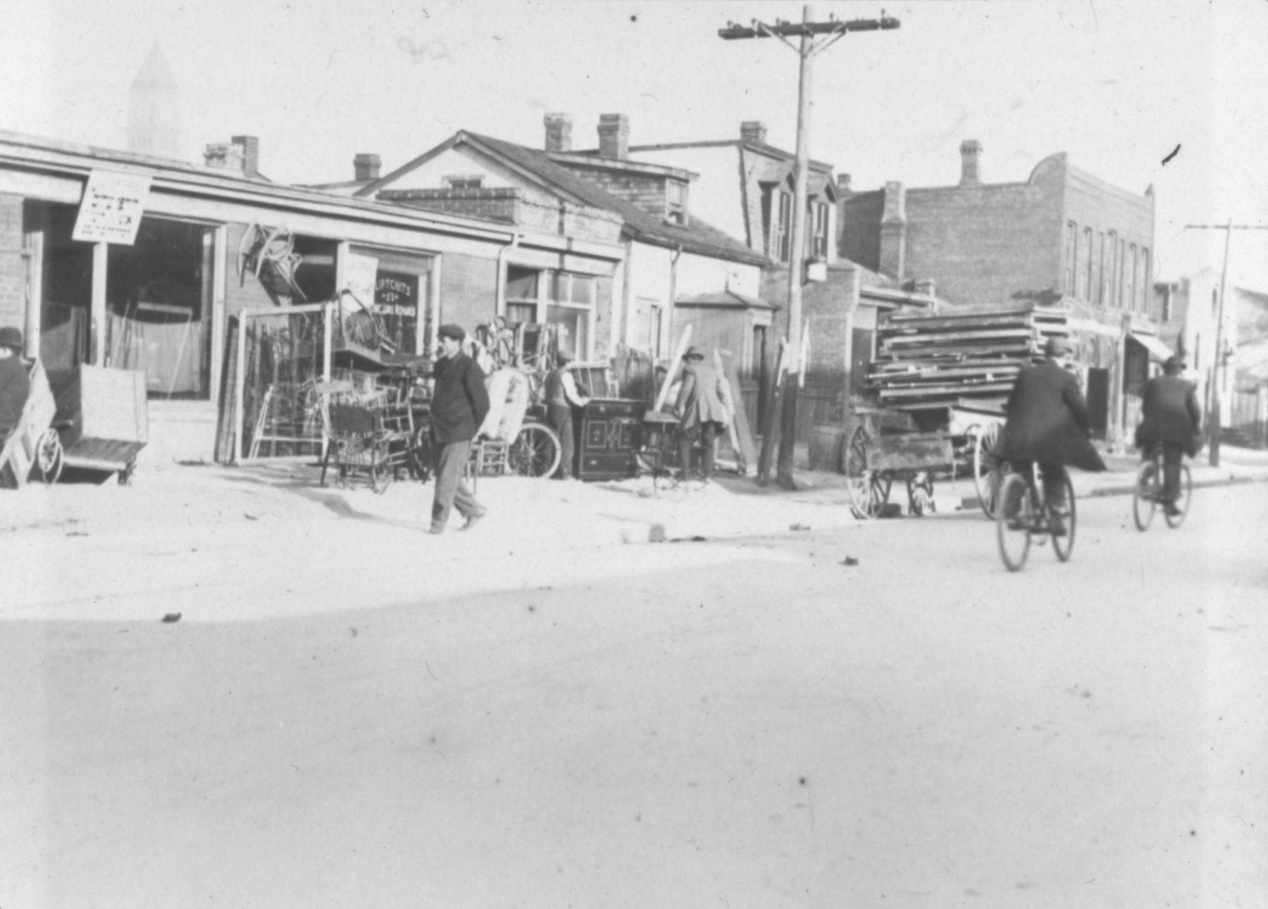 Street view of Terauley Street (now Bay Street), the Ward, ca. 1910. The main subject of the photo is the secondhand shop Liptchts (Lipchitz's). Also visible to the left of the shop is a Yiddish language sign and the Old City Hall clock tower can faintly be seen in the background.  OJA, fonds 43, item 1.