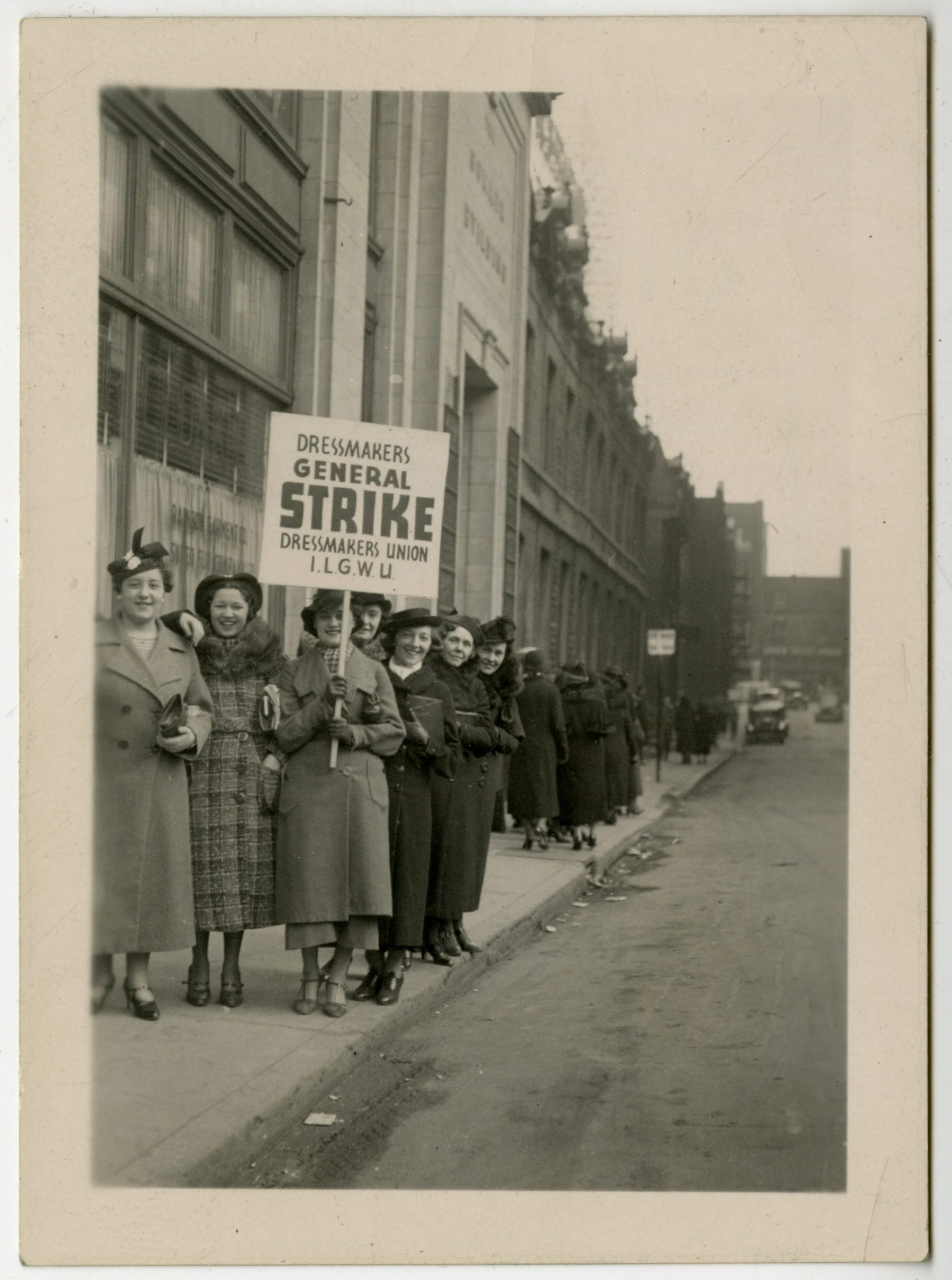 A group of women dressmakers picketing on Spadina Avenue. They are holding a sign that reads: Dressmakers General Strike, Dressmakers Union, ILGWU. The strike happened on 25 February 1931 and lasted for two-and-a-half months.   OJA, item 1440.