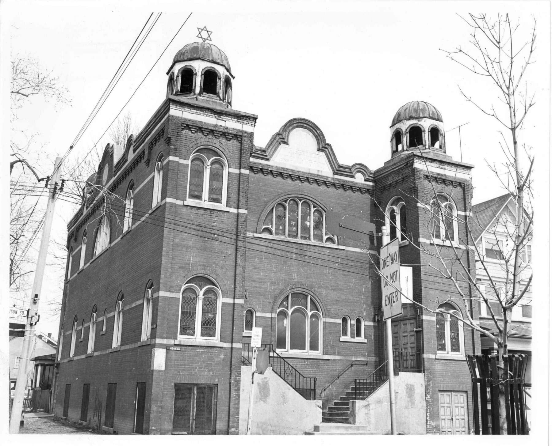 The Kiever Shul (synagogue) exterior, Toronto, 1974. The Kiever had its beginnings on Centre Avenue in the Ward. In 1923, the Kiever congregation raised enough funds to build a synagogue large enough to accommodate its growing membership. Benjamin Swartz, a Jewish architect was contracted to design the current synagogue at 25 Bellevue, which replaced the two houses that had been used for services. The Synagogue was completed in 1927, after three years of construction.   OJA, item 71.