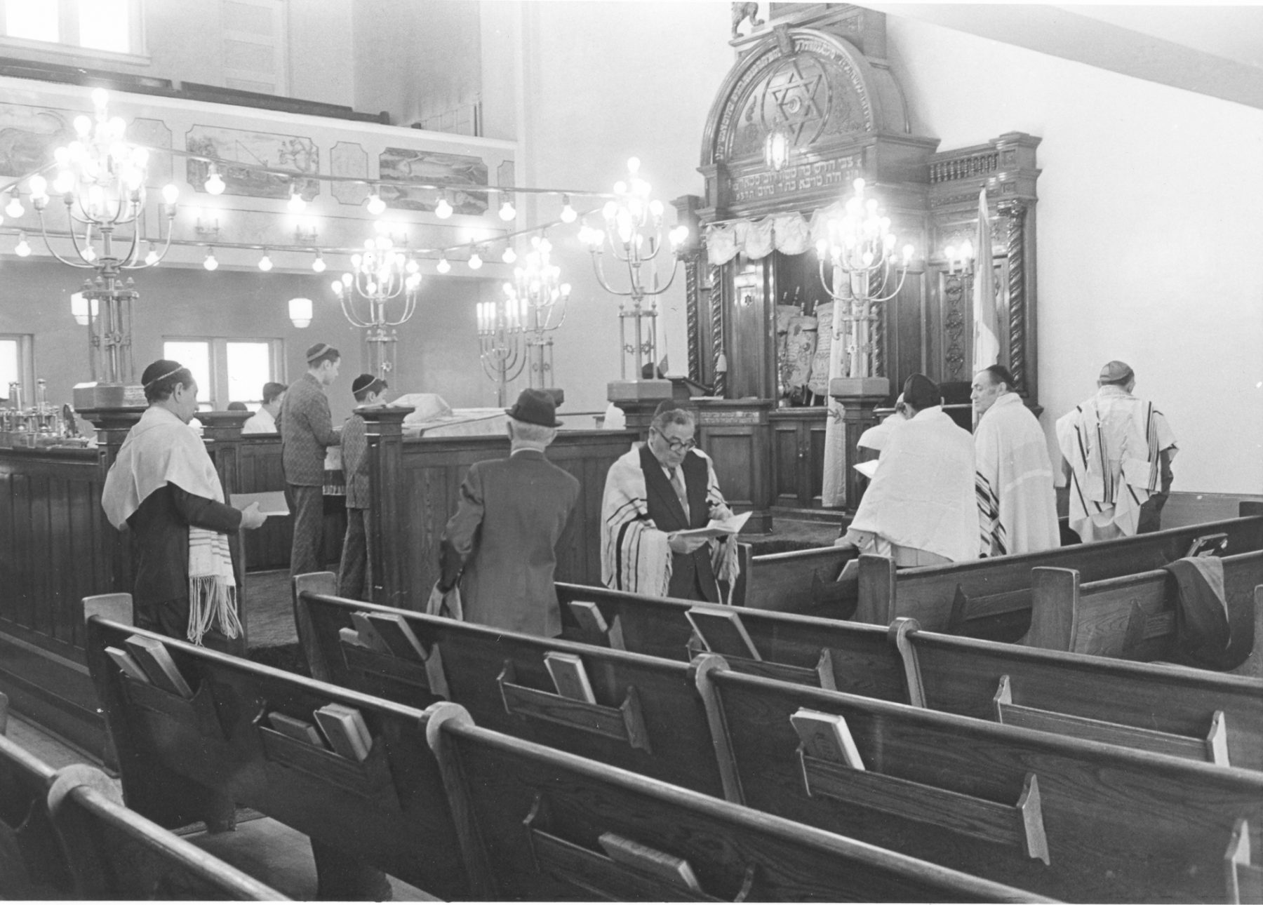 Kiever Shul interior, Apr. 1974. Leading the service from the bimah, the raised platform at the centre of the sanctuary, are Michael David and Earl David.   OJA, item 293.