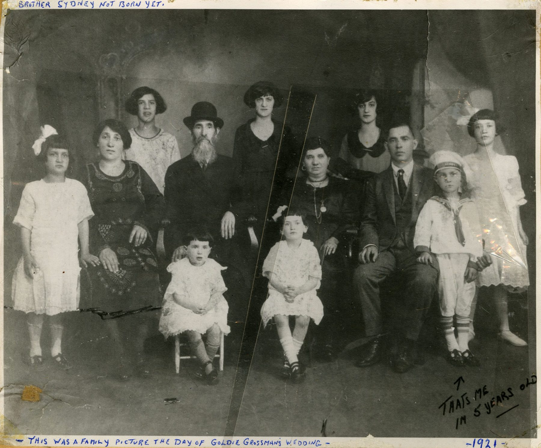 """Portrait of the Luftspring family at the Ostrovzter Synagogue on Cecil Street to mark the marriage of Max Lightstone and Goldie Grossman on 9 June 1922. In the top-left corner Sammy has indicated that his younger brother Sydney was not born yet. In the bottom right corner, Sammy annotated the photo with an arrow pointing to himself, """"That's me. I'm 5 years old.""""   OJA, fonds 82, item 1."""