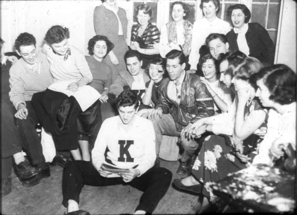 """A group of teenagers at the Brunswick Avenue YM-YWHA at a club meeting. In the early 1930s, the """"Y"""" developed educational and cultural programs to meet the demand from Toronto's Jewish youth. The club provided Jewish youth with a place to socialize. There were also organized events such as, dances, picnics, and concerts.   OJA, fonds 61, series 6, item 26."""